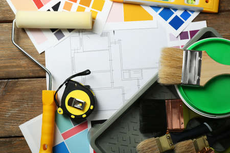 paint samples: Construction instruments, plan, colorful paint samples and brushes on wooden table background