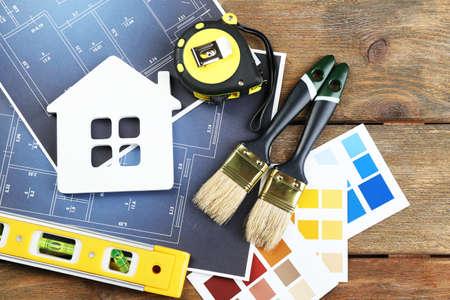 CHantillons de couleur, maison de décoration, des gants et des pinceaux sur table en bois fond Banque d'images - 50788865