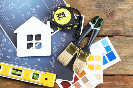 Color samples, decorative house, gloves and paintbrushes on wooden table background Stok Fotoğraf