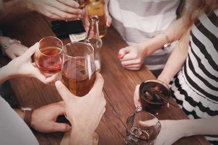 tomando alcohol: Ver en los amigos que tienen las bebidas alcohólicas en el bar, primer plano