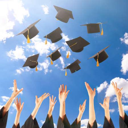 graduating seniors: Graduates hands throwing graduation hats in the sky Stock Photo
