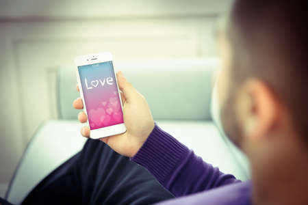 screensaver: Young man using his phone with romantic screensaver