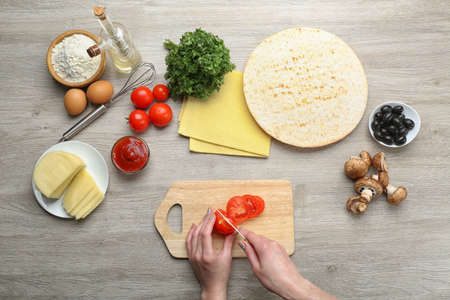 Female hands cooking pizza on wooden table, closeup Stock Photo