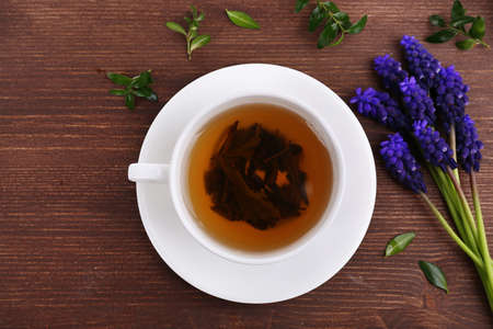 herbal plant: Cup of herbal tea with flowers on wooden table, top view
