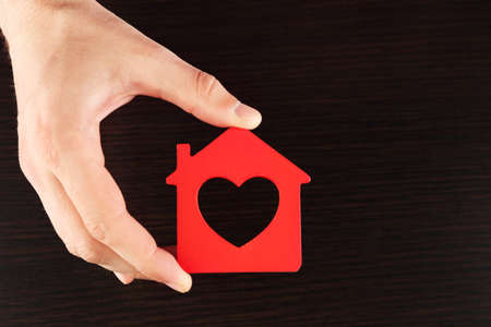 hand holding house: Female hand holding house on wooden background