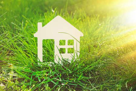 Pequeño modelo de la casa sobre el fondo de la hierba verde
