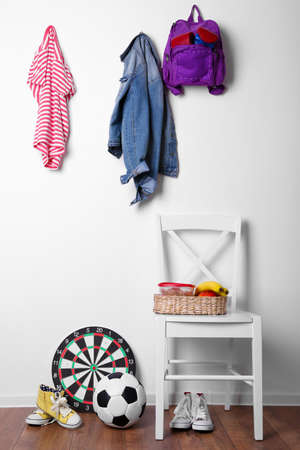 clothes rack: Children things hanging on wall and stacked in room