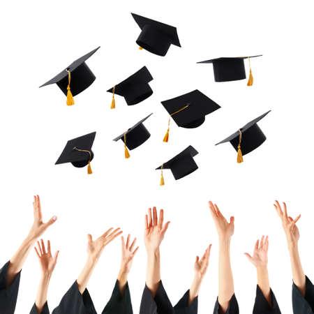 Graduados que lanzan los sombreros de graduación de manos, aislado en blanco Foto de archivo