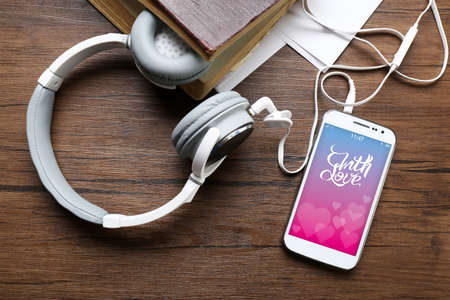 screensaver: Headphones with old book and smartphone with romantic screensaver