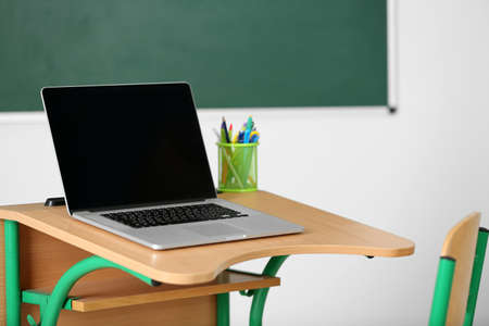school room: Wooden desk with stationery and laptop in class on blackboard background Stock Photo