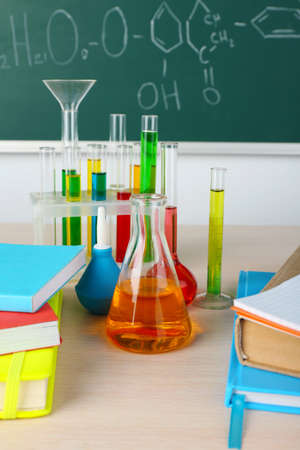 chemistry class: Desk in chemistry class with test tubes on green blackboard background Stock Photo