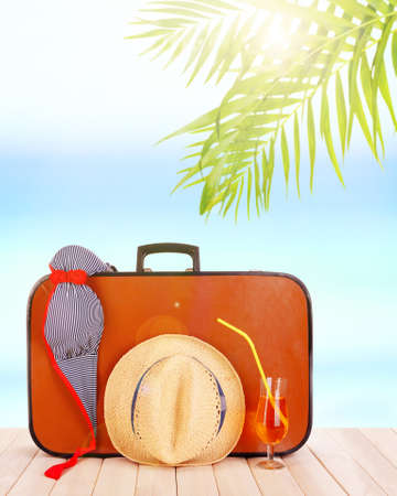 valise: Vintage valise with summer items on wooden board on sea background Stock Photo