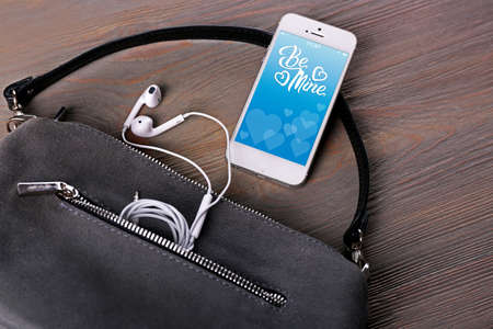 screensaver: Ladies handbag and smartphone with romantic screensaver on gray background