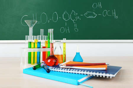 green chemistry: Desk in chemistry class with test tubes on green blackboard background Stock Photo