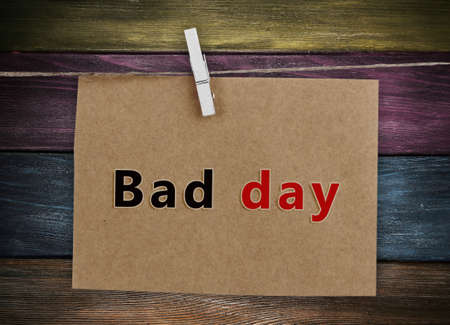 skeptic: Old sheet of paper with text Bad Day hanging on rope isolated on white
