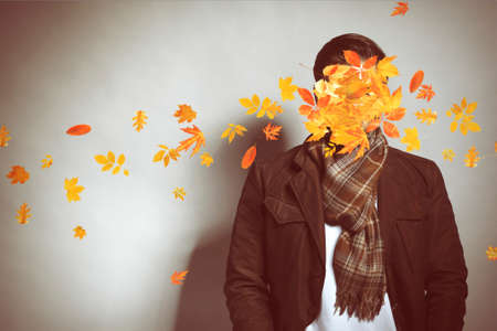 Young man and falling autumn leaves on gray background Stock Photo