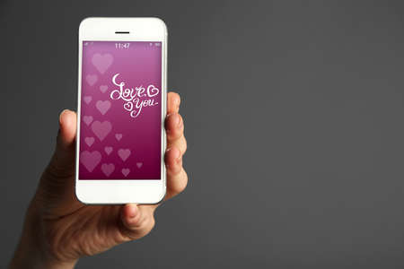 screensaver: Hand holding smart phone with romantic screensaver