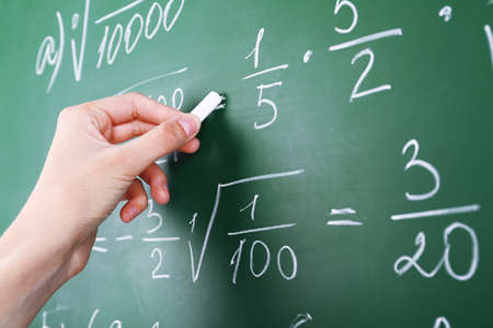 Female hand writing formulas on blackboard with chalk close up
