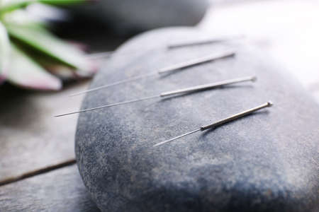 Needle for acupuncture on spa stones on table close up