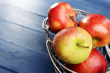 apple basket: Ripe apples in metal basket on wooden background