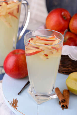 non alcoholic beverage: Glass and carafe of apple cider with fruits and spices on table close up Stock Photo