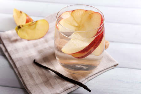 non alcoholic beverage: Glass of apple cider with fruits and vanilla stick on table close up