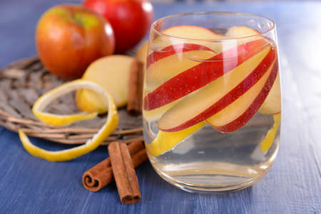 non alcoholic: Glass of apple cider with fruits and cinnamon on table close up Stock Photo