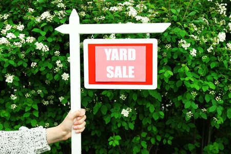 yard sign: Wooden Yard Sale sign in female hand over green bush and flowers background