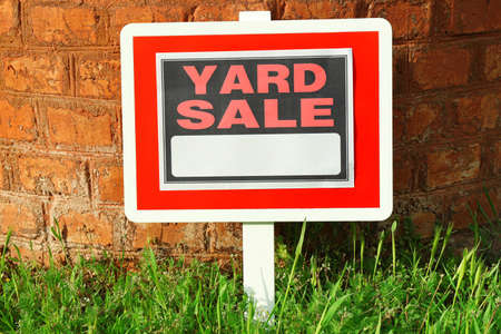 yard sign: Wooden Yard Sale sign in green grass on red brick wall background Stock Photo