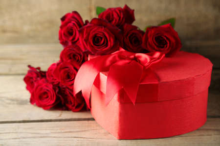 Heart shaped Valentines Day gift box with red roses on old wooden table Archivio Fotografico