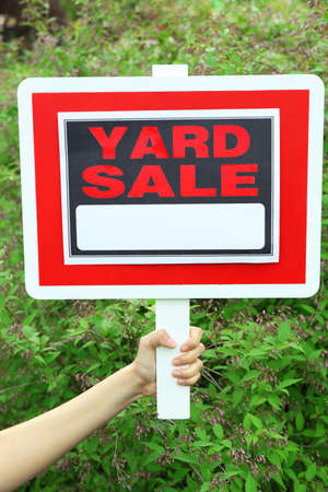 yard sign: Wooden Yard Sale sign in female hand over green grass background