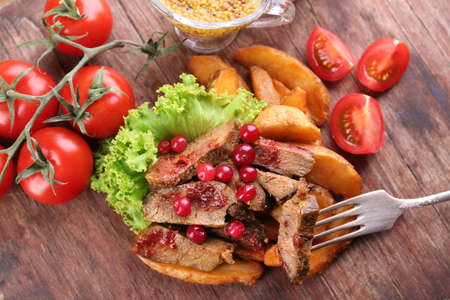 steak beef: Beef with cranberry sauce, roasted potato slices and bun on cutting board, on wooden background Stock Photo