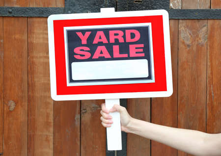 yard sign: Wooden Yard Sale sign in female hand on wooden fence background Stock Photo