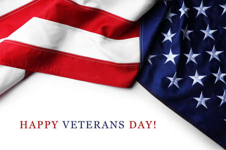Text Happy Veterans Day on white background near American flag