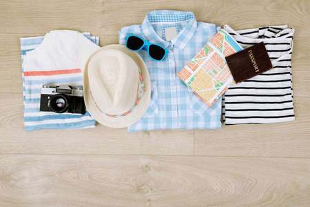 male fashion: Summer vacation clothes, shoes and hat on wooden background