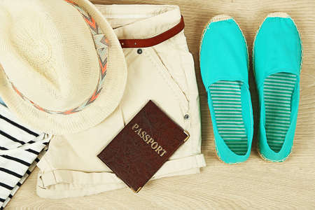 wooden shoes: Summer vacation clothes, shoes and hat on wooden background