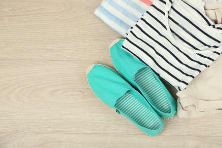 ropa de verano: ropa de vacaciones de verano, zapatos y sombrero sobre fondo de madera