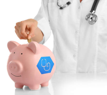 doctor putting money: Doctor in white uniform with stethoscope putting coin into pink piggy bank isolated on white