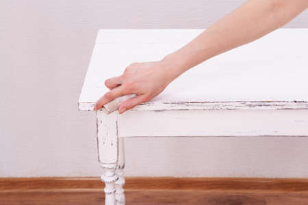 removing: Female hand removing paint from wooden table for decoration, indoors