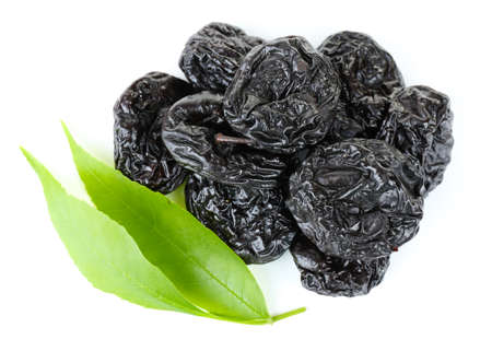 prunes: Pile of prunes with green leaves isolated on white