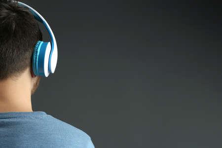 Mladý muž poslouchá hudbu na šedém pozadí