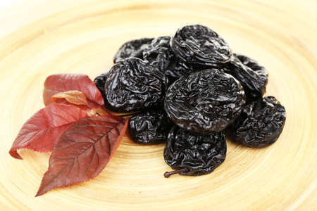 prunes: Pile of prunes with leaves on wooden background