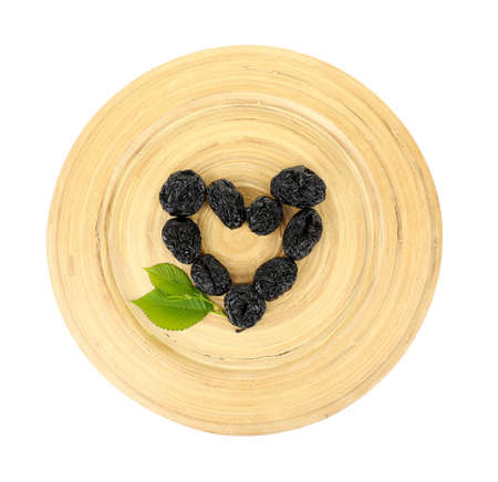 prunes: Pile of prunes with leaves on wooden tray isolated on white