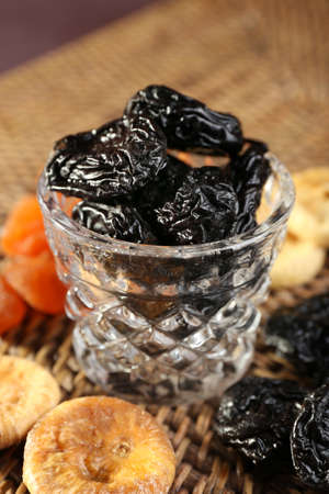 prunes: Prunes and other dried fruits on wicker mat, closeup