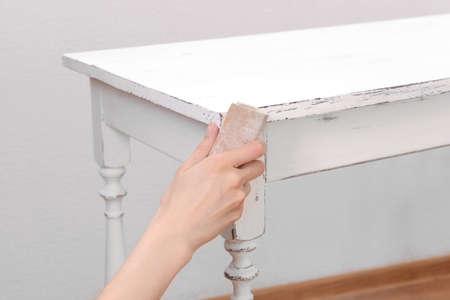 Vrouwelijke hand verwijderen van verf van houten tafel voor decoratie, binnen