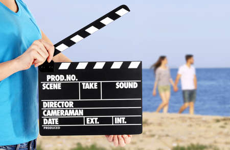 directors cut: Operator holding clapperboard during the production of film outdoor