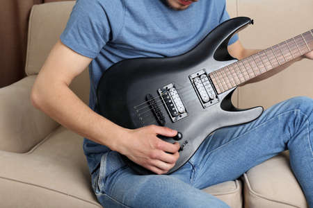 jamming: Young man with guitar on sofa in room