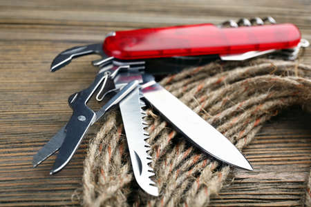 reflectance: Pocket knife with rope on wooden table close up