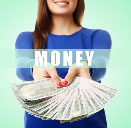 woman holding money: Woman holding money on green background Stock Photo