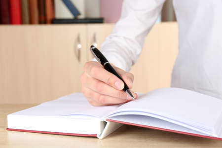 pointed arm: Hand write on notebook in office Stock Photo